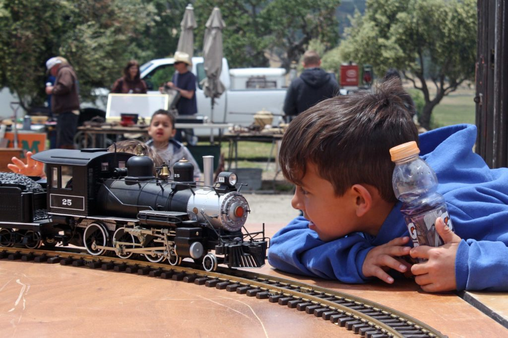 Young boy watches large scale model trains